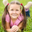 Portrait of a little girl laying on green grass — Stock Photo