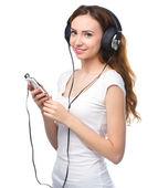 Young woman enjoying music using headphones — Stock Photo