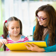 Mother is reading book with her daughter — Stock Photo #34772083