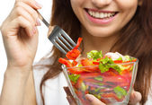 Young attractive woman is eating salad using fork — Стоковое фото