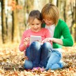 Stock Photo: Mother is reading from tablet with her daughter