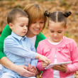 Mother is reading book with her daughter and son — Stock Photo #34845861