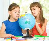 Little girls are examining globe — Stock Photo