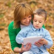 Mother is reading from tablet with her son — Stock Photo #34899295