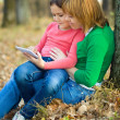 Mother is reading from tablet with her daughter — Stock Photo