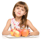Little girl with red apples — Stock Photo