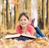 Little girl is reading a book outdoors — Foto Stock