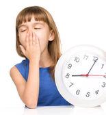 Malá holčička se drží velké hodiny — Stock fotografie