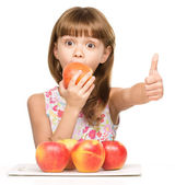 Little girl with apples is showing thumb up sign — Stock Photo