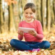 Little girl is reading from tablet — Stock Photo