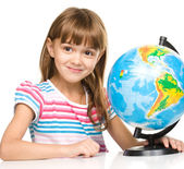 Little girl is examining globe — 图库照片