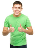 Cheerful young man showing thumb up sign — Stok fotoğraf