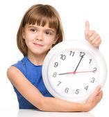Liten flicka håller stora klocka — Stockfoto