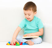 Boy is playing with puzzle — Stock Photo