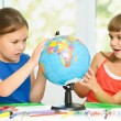 Little girls are examining globe — Stock Photo #38931521