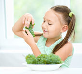 Cute little girl is eating green grapes — Stock Photo