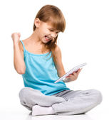 Young girl is playing game using tablet — Stock Photo