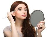 Young woman is applying eyeshadow — Стоковое фото