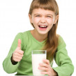 Happy little girl with a glass of milk — Stock Photo