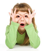 Astonished little girl is showing glasses gesture — Stock Photo