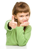 Little girl is showing thumb up sign — Stock Photo