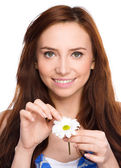 Young woman is tearing up daisy petals — Stock Photo