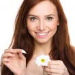 Young woman is tearing up daisy petals — Stock Photo #43054323