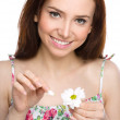 Young woman is tearing up daisy petals — Stock Photo #43142715