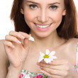 Young woman is tearing up daisy petals — Stock Photo #43142733
