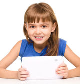 Young cheerful girl is using tablet — Stock Photo