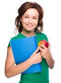 Fille jeune étudiant tient du livre et la pomme — Photo