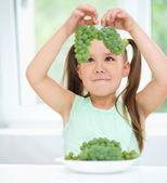 かわいい女の子が緑色のブドウを見てください。 — ストック写真