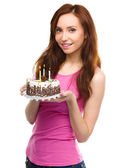 Young woman with anniversary cake — Stockfoto