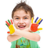 Portrait of a cute boy playing with paints — Stockfoto