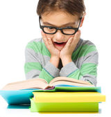 Astonished little boy is reading a book — Stock Photo