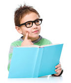 Young boy is daydreaming while reading book — Stockfoto