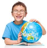 Little boy is examining globe — ストック写真