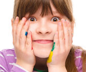Little girl is holding her face in astonishment — Stock Photo