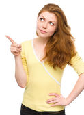 Portrait of a young woman pointing to the left — Stock Photo