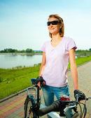 Genç kadın bisiklet duruyor — Stok fotoğraf