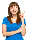 Portrait of a young woman pointing to the right — Stock Photo