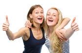 Two young happy women showing thumb up sign — Photo