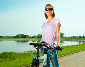 Young woman is standing behind bicycle — Foto Stock
