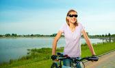 年轻的女人正站在自行车后面 — 图库照片
