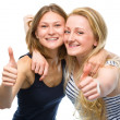 Two young happy women showing thumb up sign — Stock Photo #48728785