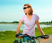 Young woman is standing behind bicycle — Stock Photo