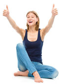 Young happy woman is showing thumb up sign — Stockfoto