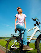 Young woman is sitting on her bicycle — Stock Photo