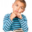 Young boy is daydreaming while reading book — Stock Photo #49443949