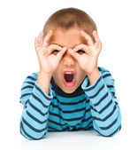Astonished little boy is showing glasses gesture — Stock Photo